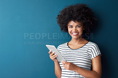 Buy stock photo Studio portrait of an attractive young woman using a digital tablet against a blue background