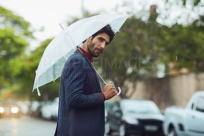 Buy stock photo Cropped shot of a handsome young businessman on his morning commute in the rain