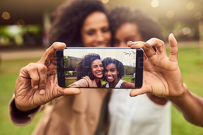 Buy stock photo Cropped shot of two female best friends taking a picture in a public park