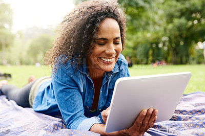 Buy stock photo Cropped shot of a beautiful young woman using a tablet in a public park