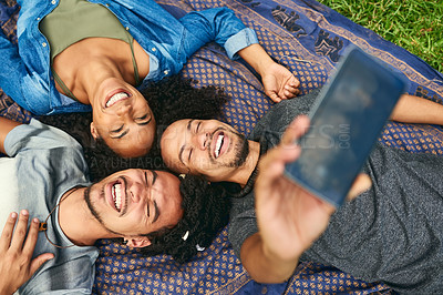 Buy stock photo High angle shot of a group of friends taking a selfie while lying down in a public park
