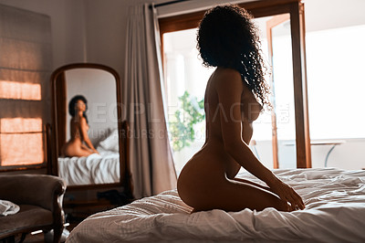 Buy stock photo Shot of a beautiful young woman sitting naked on the bed and admiring herself in the mirror