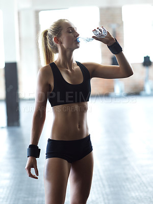 Buy stock photo Cropped shot of an attractive young woman drinking water  while taking a break from a work out in the gym