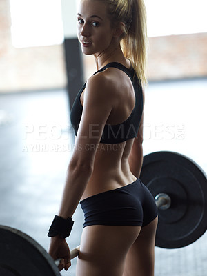 Buy stock photo Cropped shot of an attractive young woman lifting weights in the gym