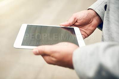 Buy stock photo Closeup shot of an unrecognizable businessman using a digital tablet outdoors