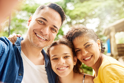 Buy stock photo Cropped portrait of a young family of three taking selfies in the park