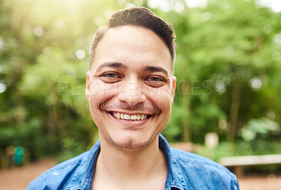 Buy stock photo Cropped portrait of a handsome young man standing outside in the park