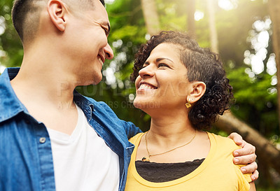 Buy stock photo Cropped shot of an affectionate young couple standing face to face outside in the park