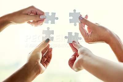 Buy stock photo Closeup shot of four unrecognizable people joining puzzle pieces together