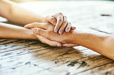 Buy stock photo Closeup shot of a man and woman holding hands in comfort on a table