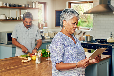 Buy stock photo Shot of a mature woman using a digital tablet while preparing a meal at home with her husband