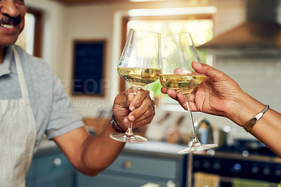 Buy stock photo Cropped shot of a mature couple toasting with wine in the kitchen at home