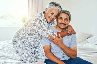 Buy stock photo Portrait of a cheerful mature couple holding each other while being seated on a bed at home during the day