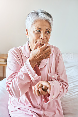Buy stock photo Shot of a cheerful mature woman enjoying a piece of chocolate while being seated on a bed at home in the morning