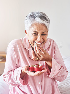 Buy stock photo Portrait of a cheerful mature woman enjoying a piece of chocolate while being seated on a bed at home in the morning