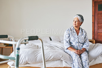 Buy stock photo Shot of a confident mature woman looking outside trough her window while contemplating at home during the day