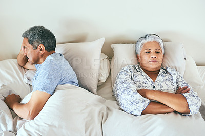 Buy stock photo Shot of an irritated looking mature couple lying in bed facing away from each other after having an argument at home during the day