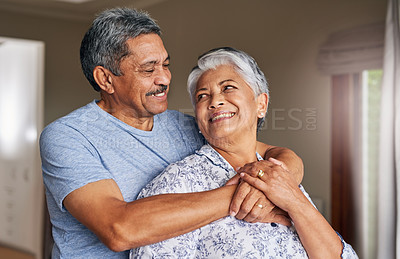 Buy stock photo Shot of a cheerful mature couple holding each other at home during the day