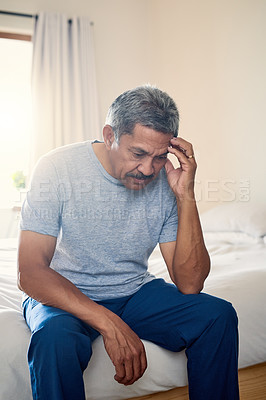 Buy stock photo Shot of a stressed out mature man holding his head in discomfort while being seated on his bed at home