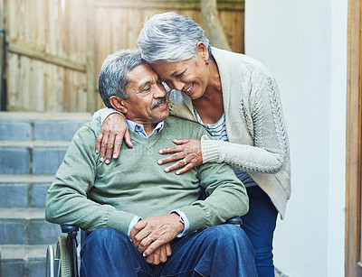 Buy stock photo Shot of a cheerful elderly man seated in a wheelchair while being held by his loving wife outside at home during the day