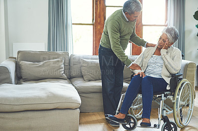 Buy stock photo Shot of a worried looking elderly woman seated in a wheelchair while being supported and held by her husband inside at home during the day