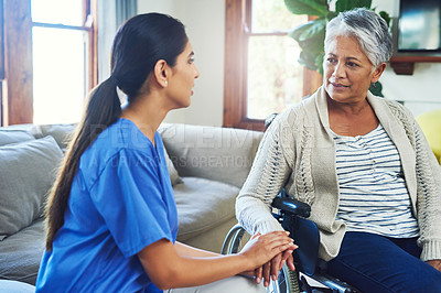 Buy stock photo Shot of a worried looking elderly woman seated in a wheelchair while a female nurse holds her hand for support inside at home during the day