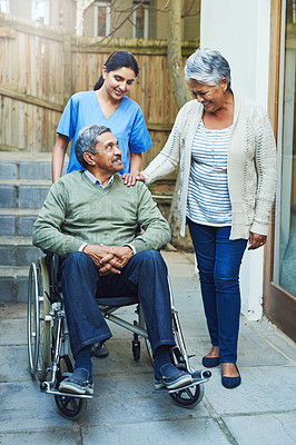 Buy stock photo Shot of a cheerful elderly man seated in a wheelchair while being supported by his wife and a female nurse at home during the day