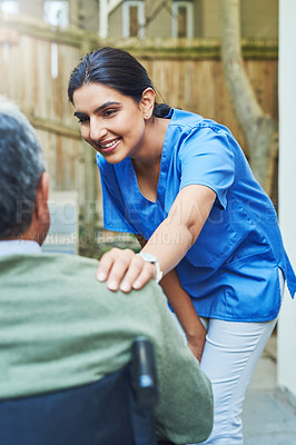 Buy stock photo Shot of a cheerful young female nurse holding the shoulder of a patient in a wheelchair for support outside at home