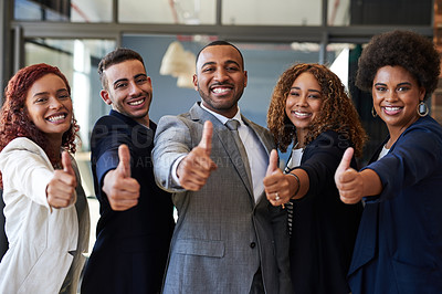 Buy stock photo Portrait of a group of businesspeople showing thumbs up together in an office