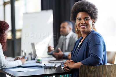Buy stock photo Portrait of a young businesswoman sitting in an office with her colleague in the background