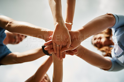 Buy stock photo Low angle shot of a family of four standing with their hands in a huddle