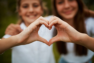 Buy stock photo Closeup shot of two young sisters' hands making a heart shape