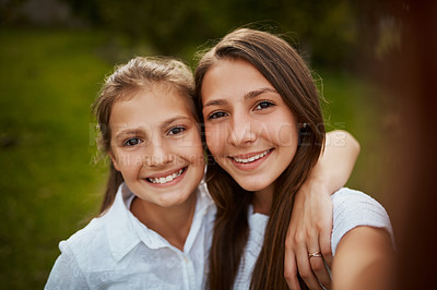 Buy stock photo Cropped portrait of two young sisters taking selfies in the park