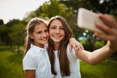 Buy stock photo Cropped shot of two young sisters taking selfies in the park