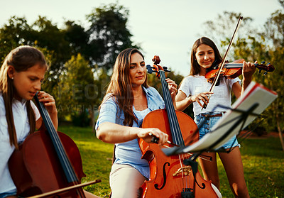 Buy stock photo Cropped shot of a beautiful mother playing instruments with her adorable daughters outdoors