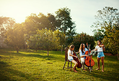 Buy stock photo Shot of a beautiful mother playing instruments with her adorable daughters outdoors