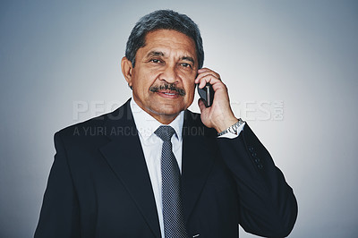 Buy stock photo Studio portrait of a mature businessman talking on a cellphone against a grey background