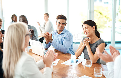 Buy stock photo Shot of a group of young businesspeople applauding during a meeting in a modern office