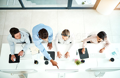 Buy stock photo High angle shot of a young man helping his colleagues in a call center