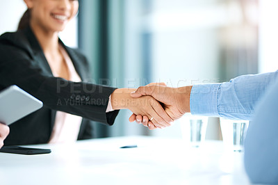 Buy stock photo Shot of a young businesswoman shaking hands with a businessman during a meeting in a modern office