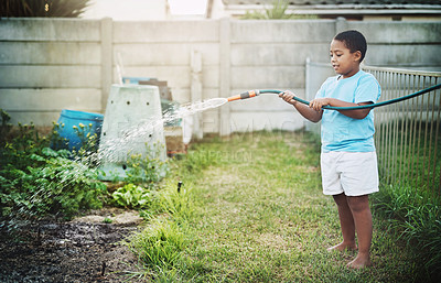 Buy stock photo Shot of a little boy using a hose pipe to water the garden outdoors