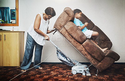 Buy stock photo Shot of a grandmother vacuuming under a couch which her grandson is lying on at home