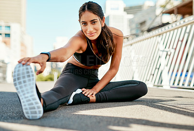 Buy stock photo Portrait of a sporty young woman stretching before her run in the city