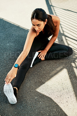Buy stock photo Shot of a sporty young woman stretching before her run in the city