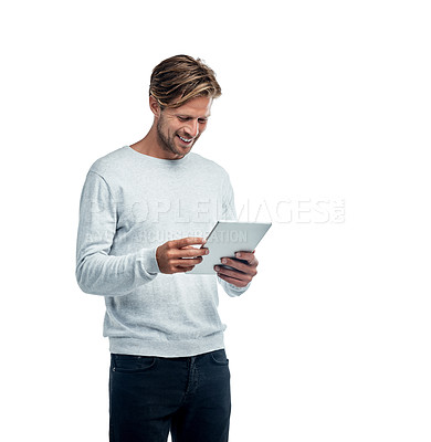 Buy stock photo Studio shot of a handsome young man using his tablet while standing against a white background