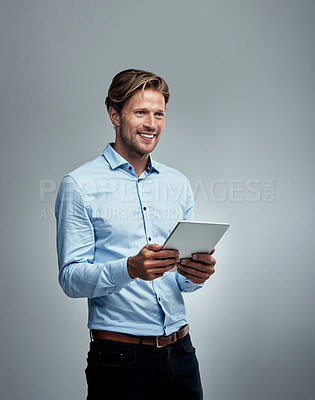 Buy stock photo Studio shot of a handsome young businessman using a digital tablet against a grey background