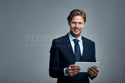 Buy stock photo Studio portrait of a handsome young businessman using a digital tablet against a grey background