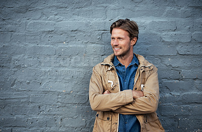 Buy stock photo Cropped shot of a handsome young man standing with his arms folded against a grey brick wall