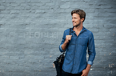 Buy stock photo Cropped shot of a handsome young man standing with his bag against a grey brick wall