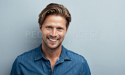 Buy stock photo Studio portrait of a handsome young man standing against a grey background